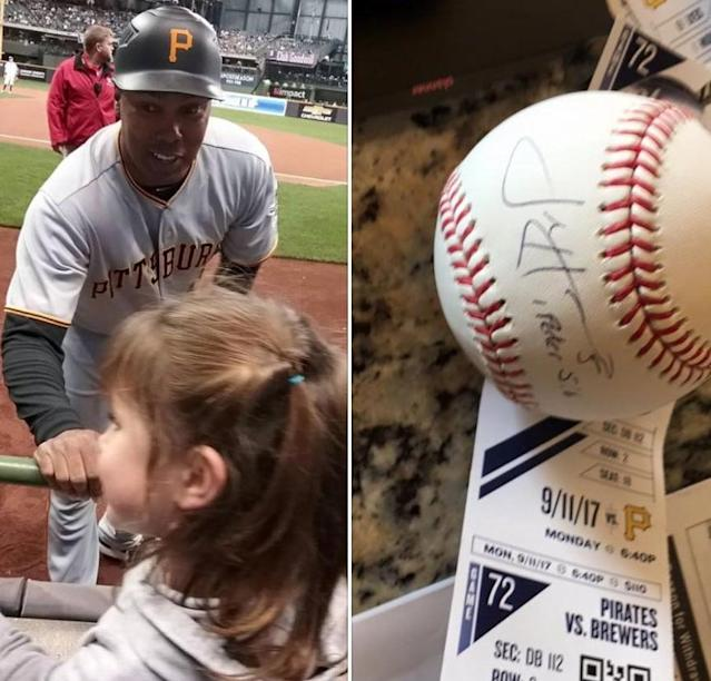 Pirates first base coach Kimera Bartee gives a young fan a baseball on behalf of Josh Harrison. (Pirates on Twitter)