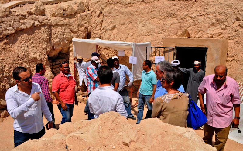 Journalists and members of an Egyptian archaeological team stand near artifacts discovered in a 3,500-year-old tomb in the Draa Abul Nagaa necropolis, near the southern city of Luxor, on April 18, 2017 - Credit: AFP