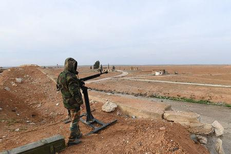 A Syrian Army soldier loyal to Syria's President Bashar al-Assad forces stands next to a military weapon in Idlib