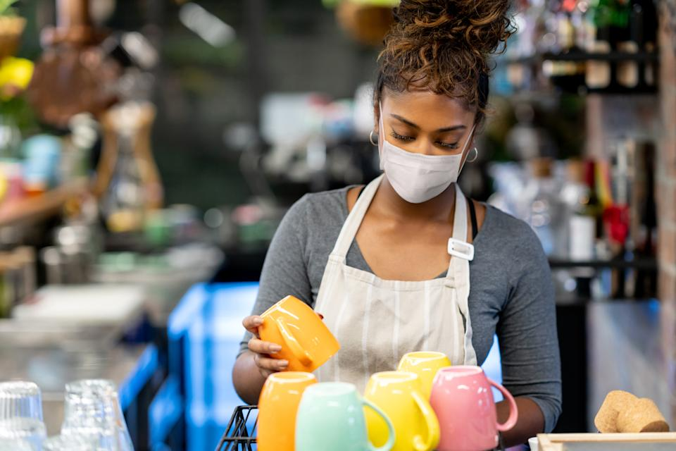 Waitress working at a cafe wearing a facemask while washing the dishes during the COVID-19 pandemic