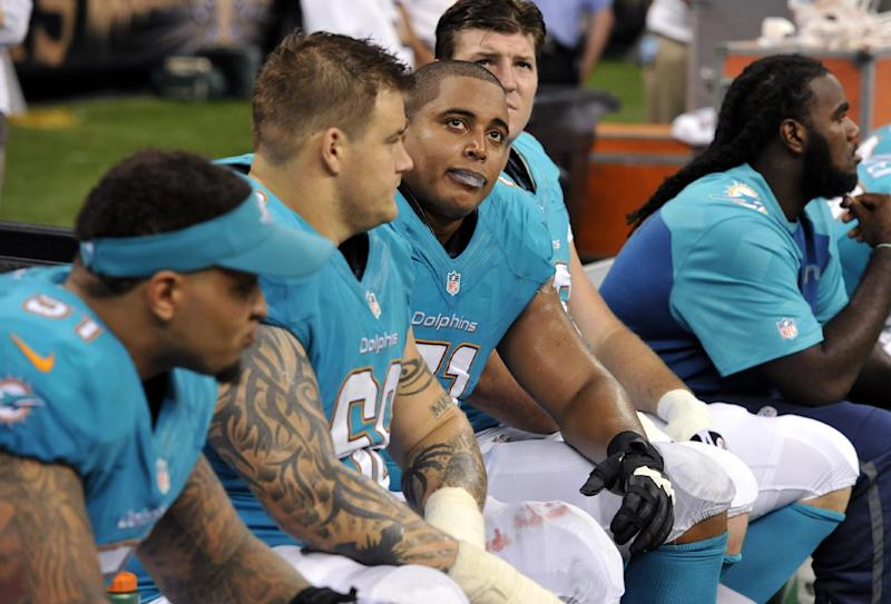 FILE - In this Sept. 30, 2013 file photo, Miami Dolphins guard Richie Incognito (68), second from left, and tackle Jonathan Martin (71), third from left, sit on the bench in the second half of an NFL football game against the New Orleans Saints in New Orleans. Two people familiar with the situation say suspended Dolphins guard Incognito sent text messages to teammate Jonathan Martin that were racist and threatening. The people spoke to The Associated Press on condition of anonymity because the Dolphins and NFL haven't disclosed the nature of the misconduct that led to Incognito's suspension. Martin remained absent from practice Monday, Nov. 4, 2013, one week after he suddenly left the team. (AP Photo/Bill Feig, File)