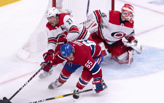 Carolina Hurricanes defenseman Justin Faulk takes Montreal Canadiens' Andrew Shaw out from in front of goaltender Curtis McElhinney during the third period of an NHL hockey game Tuesday, Nov. 27, 2018, in Montreal. (Paul Chiasson/The Canadian Press via AP)
