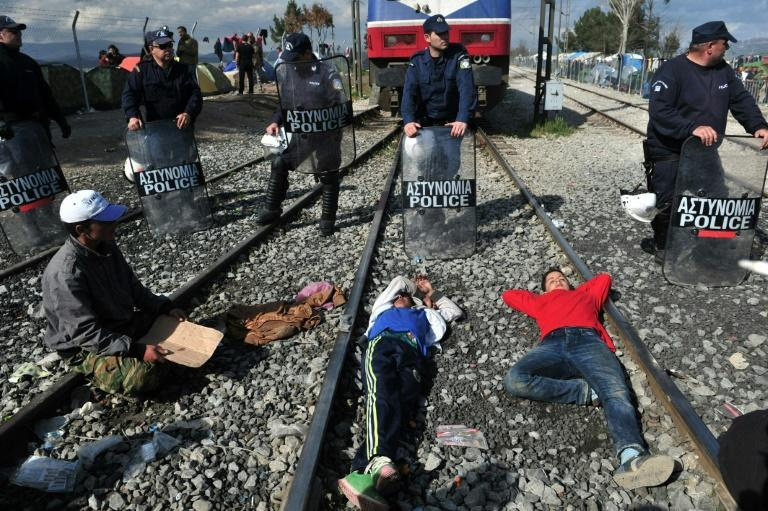 People sit and lie on train tracks in front of Greek policemen during a protest of migrants and refugees to call for the opening of the borders, at the Greek-Macedonian border near the Greek village of Idomeni on March 3, 2016