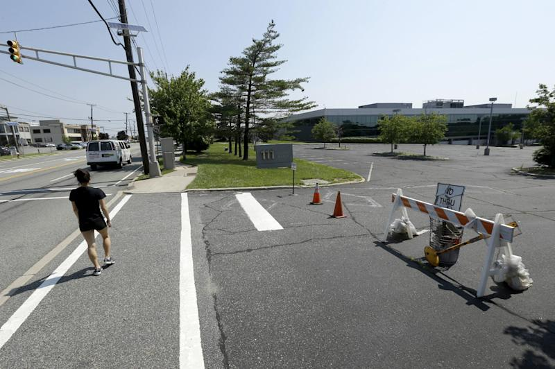 In this photograph taken Friday, June 21, 2013, in Englewood Cliffs, N.J., a pedestrian walks by an empty parking lot near a building on Sylvan Avenue. The electronics giant LG is planning to build a gleaming new headquarters here. One of the biggest opponents is New York's Metropolitan Museum of Art, which contends the building will ruin the view of the Palisades, a line of steep cliffs along the Hudson River, that is visible from the Cloisters. The museum is joined by numerous environmental groups and local citizens who say the building will be an eyesore on one of the country's most beautiful spaces. (AP Photo/Julio Cortez)