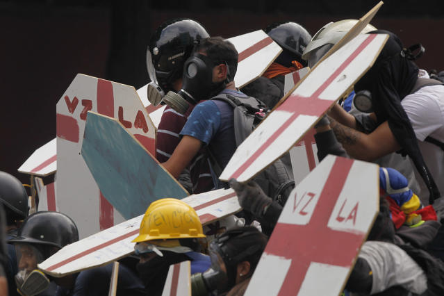 <p>Anti-government protesters use homemade shields as they face off with security forces blocking their march from reaching the National Assembly in Caracas, Venezuela, Wednesday, May 3, 2017. (AP Photo/Fernando Llano) </p>