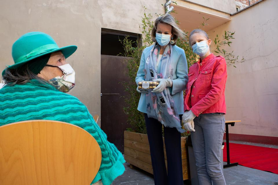 TOPSHOT - Queen Mathilde of Belgium and Princess Eleonore wear mouth masks against the spread of COVID-19, as she distributes food packages during a royal visit to the Kamiano restaurant of the homeless shelter of the Sant Egidio community in Brussels on May 14, 2020. (Photo by Alain ROLLAND / various sources / AFP) / Belgium OUT (Photo by ALAIN ROLLAND/BELGA/AFP via Getty Images)