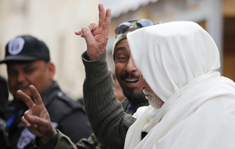 An elderly Libyan fighter who fought in the Libyan war of independence against the Italians, between 1928 and 1932, Mohammed Darsi, 85, right, flashes the victory sign along with his son, Khalifa Darsi, center, who was one of the rebels that fought in the Libyan revolution in 2011 that ousted Moammar Gadhafi, during the second anniversary celebration of the revolution in Benghazi, Libya, Sunday, Feb, 17, 2013. (AP Photo/Mohammad Hannon)