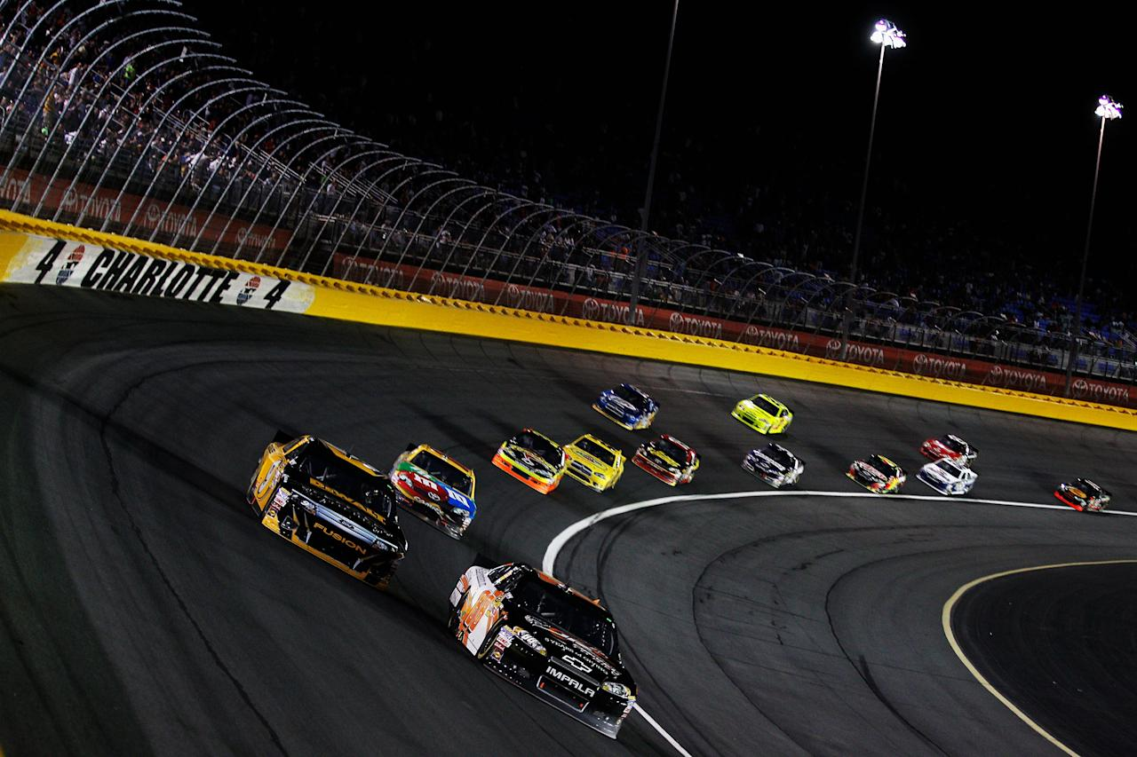 CHARLOTTE, NC - MAY 19:  Dale Earnhardt Jr., driver of the #88 Dale Jr. Foundation/National Guard/Diet Mountain Dew Chevrolet, races Marcos Ambrose, driver of the #9 DEWALT Ford, during the NASCAR Sprint All-Star Race at Charlotte Motor Speedway on May 19, 2012 in Charlotte, North Carolina.  (Photo by Chris Graythen/Getty Images)