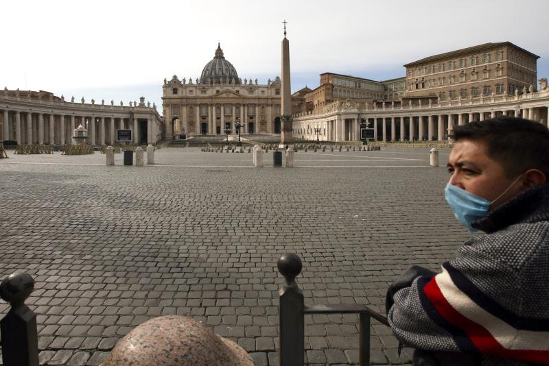 A man wears a mask as he looks at an empty St. Peter's Square after the Vatican erected a new barricade at the edge of the square, in Rome, Tuesday, March 10, 2020.