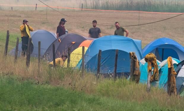 Wildland firefighters from out of province stand outside their tents at a B.C. Wildfire Service camp in Salmon Arm, B.C., last week.  (The Canadian Press/Darryl Dyck - image credit)