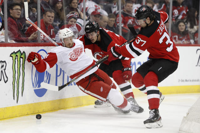 Detroit Red Wings defenseman Alex Biega (3) slips as New Jersey Devils center Pavel Zacha (37) tries to get control of the puck wiht Devils left wing Miles Wood (44) defending Biega during the second period of an NHL hockey game, Thursday, Feb. 13, 2020, in Newark, N.J. (AP Photo/Kathy Willens)