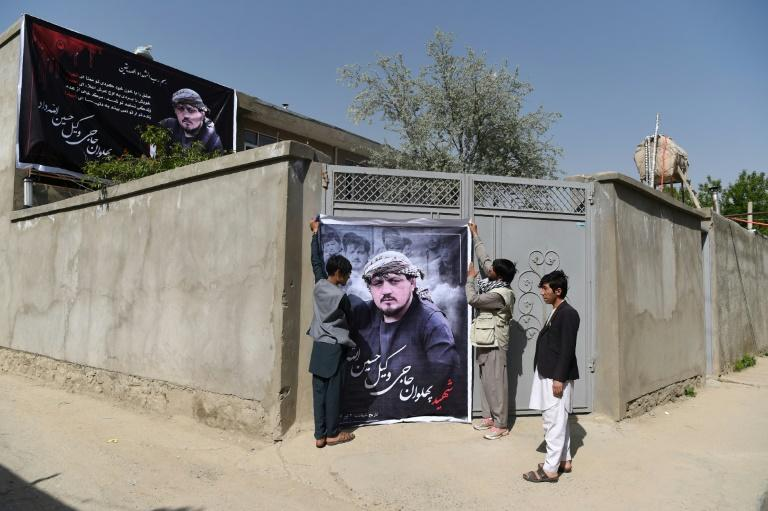 Relatives of Wakil Hussain Allahdad, 32, one of the 57 victims of a suicide attack on a voter registration centre in Kabul, hang up a banner bearing his picture outside his house in the Afghan capital on April 23, 2018