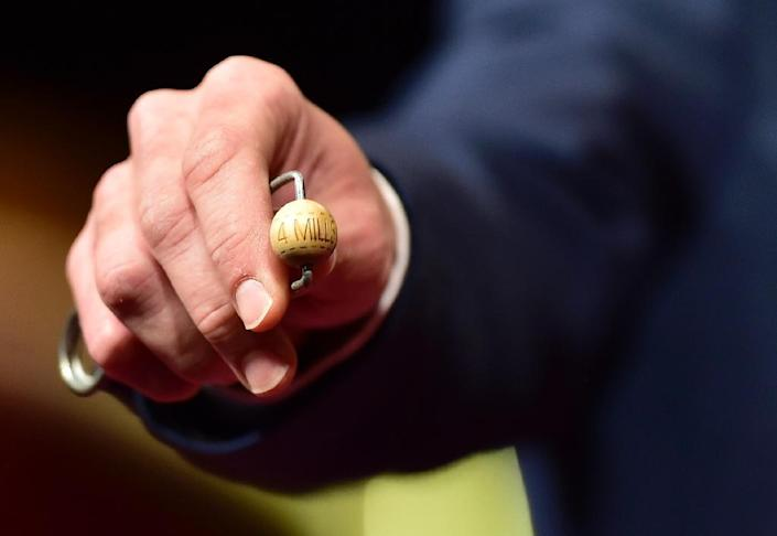 """An official shows the """"El Gordo"""" ball in Madrid, on December 22, 2016 (AFP Photo/GERARD JULIEN)"""