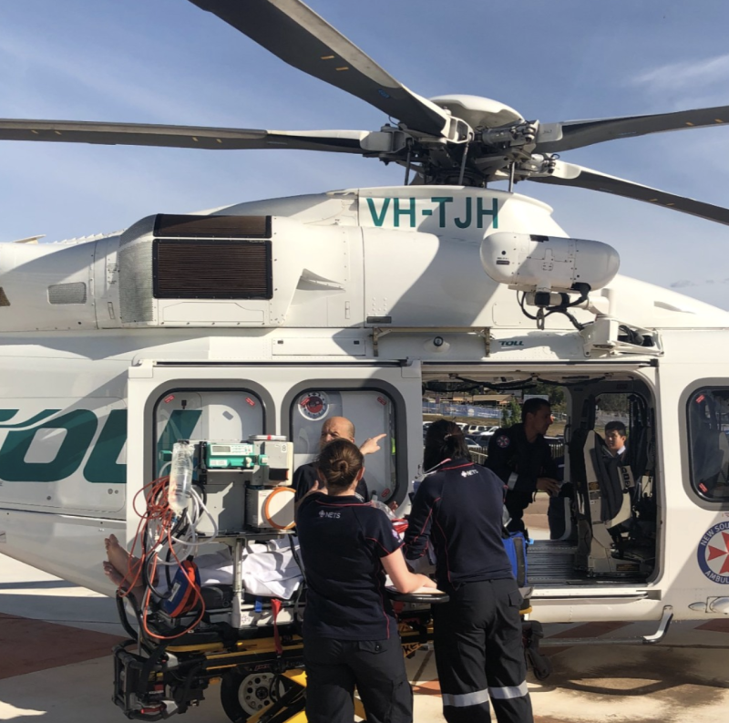 A Toll crew are pictured tending to an injured person next to a helicopter. Source: Toll