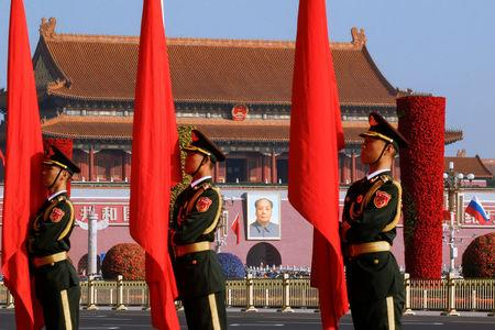 Chinese honour guards stand to attention near a portrait of China's late Chairman Mao Zedong before a welcoming ceremony for Russian Prime Minister Dmitry Medvedev at the Great Hall of the People in Beijing