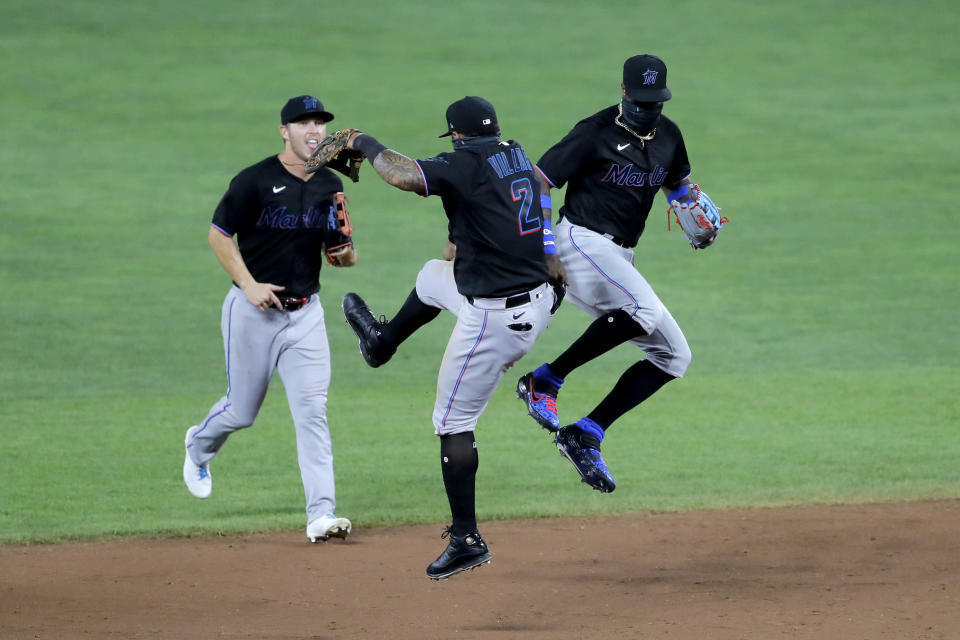 Miami Marlins shortstop Jonathan Villar (2) and center fielder Monte Harrison, right, celebrate after defeating the Baltimore Orioles 2-1 in the second game of a doubleheader, Wednesday, Aug. 5, 2020, in Baltimore. Marlins' Corey Dickerson, left, looks on. (AP Photo/Julio Cortez)