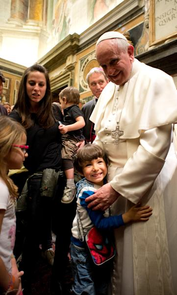 In this photo released by Vatican newspaper L'Osservatore Romano, Pope Francis hugs a child during a meeting with the Italian pro-life movement, at the Vatican Friday, April 11, 2014. (AP Photo/L'Osservatore Romano)