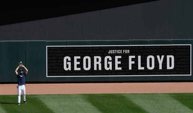 Max Kepler of the Minnesota Twins catches a fly ball in right field in front of the banner honouring George Floyd before a game last July. (Getty Images - image credit)