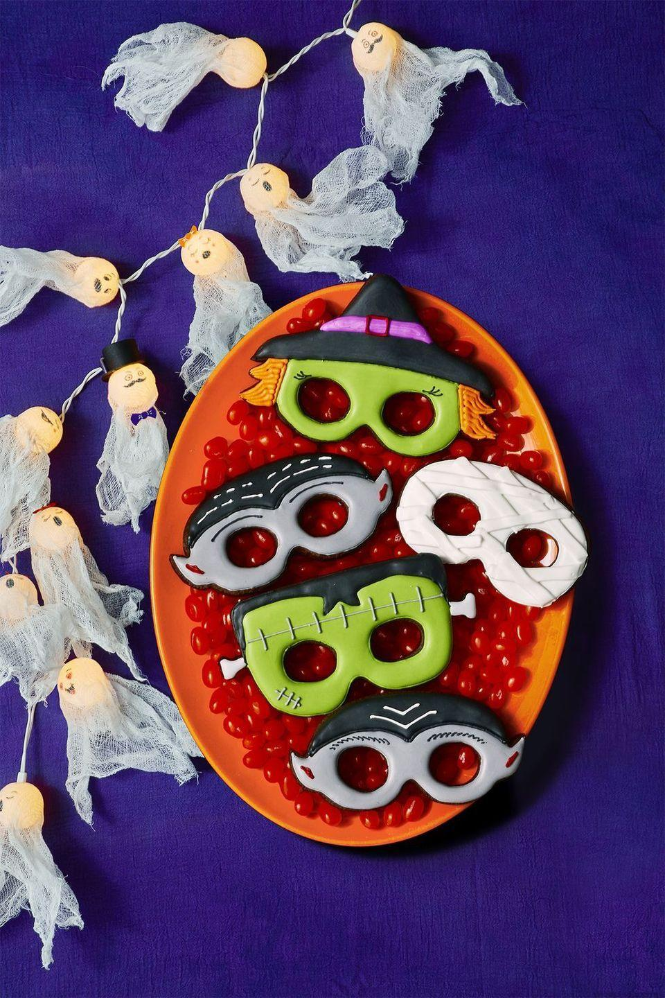 """<p>Cutest cookies ever? Just make a batch of sugar cookie dough, then use a <a href=""""https://members.easypeasyandfun.com/downloads/halloween-printable-masks/"""" rel=""""nofollow noopener"""" target=""""_blank"""" data-ylk=""""slk:mask template"""" class=""""link rapid-noclick-resp"""">mask template</a> to carve out the shape of a witch, vampire, mummy, and Frankenstein.</p><p><a href=""""https://www.womansday.com/food-recipes/food-drinks/recipes/a12008/basic-sugar-cookies-recipe-wdy1212/"""" rel=""""nofollow noopener"""" target=""""_blank"""" data-ylk=""""slk:Get the Basic Sugar Cookies recipe."""" class=""""link rapid-noclick-resp""""><strong><em>Get the Basic Sugar Cookies recipe.</em></strong></a></p>"""