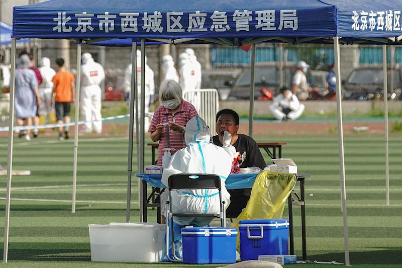 BEIJING, CHINA - JUNE 15: A Chinese nurse wearing a protective suit takes a nucleic acid test from a man at Guangan Sport Center for citizens who visited or live near the Xinfadi Market on June 14, 2020 in Beijing, China. From June 11 to June 14, Beijing reported a total of 79 new confirmed cases of new coronary pneumonia (covid-19), the number of new infection has risen after no new cases for nearly two months. (Photo by Lintao Zhang/Getty Images)