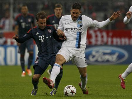Manchester City's Javi Garcia (R) fights for the ball with Bayern Munich's Mario Goetze during their Champions League Group D soccer match in Munich December 10, 2013. REUTERS/Michaela Rehle
