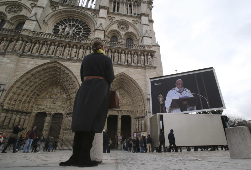 A woman watches the inauguration of Pope Francis on a giant screen outside Notre Dame cathedral, Paris, Tuesday, March 19, 2013. Pope Francis urged princes, presidents, sheiks and thousands of ordinary people gathered for his installation Mass on Tuesday to protect the environment, the weakest and the poorest, mapping out a clear focus of his priorities as leader of the world's 1.2 billion Catholics. (AP Photo/Michel Euler)