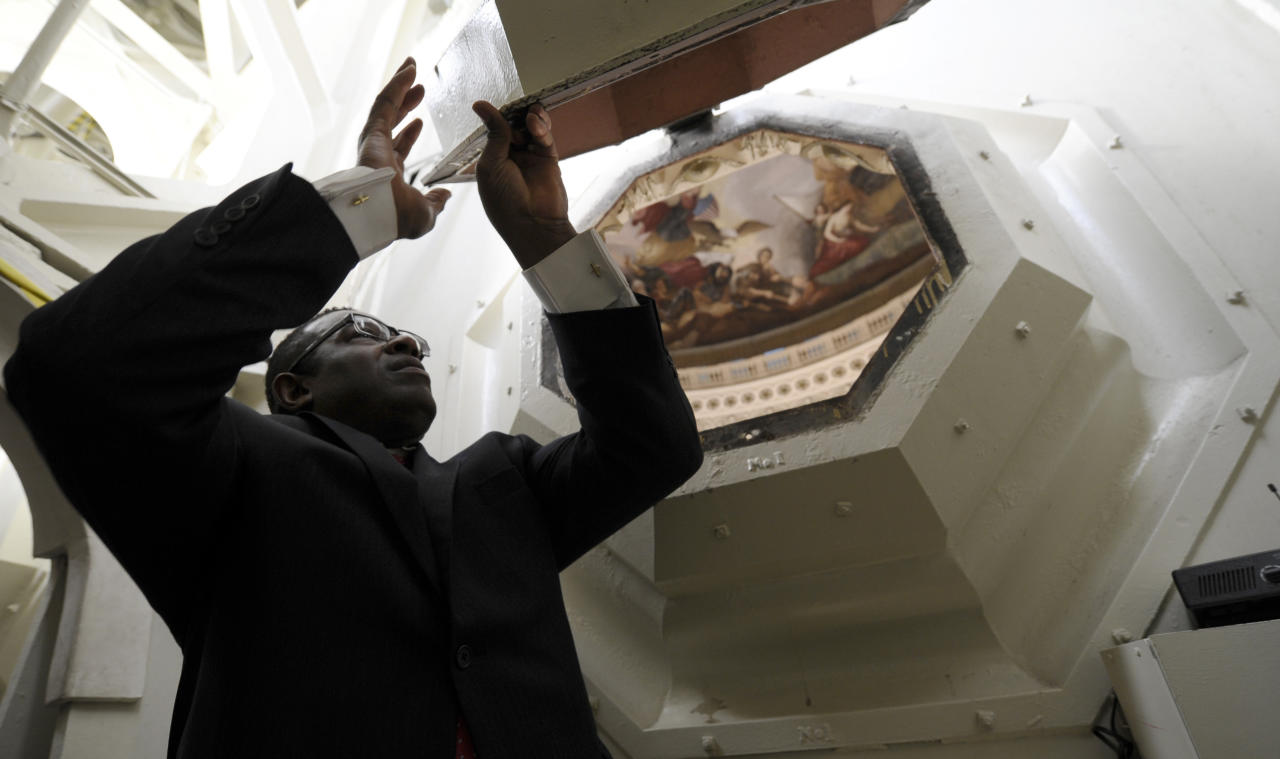 FILE - In this Dec. 19, 2013 file photo, Eugene Poole Jr., a project manager for the Capitol dome restoration project, lifts one of the coffer windows in the ceiling of the Capitol dome during a media tour on Capitol Hill in Washington. A world-famous symbol of democracy is going under cover, as workers start a two-year, $60 million renovation of the U.S. Capitol dome. Curved rows of scaffolds, like Saturn's rings, will encircle it next spring, enabling contractors to strip multiple layers of paint and repair more than 1,000 cracks and broken pieces. The dome will remain illuminated at night and partly visible through the scaffolding and paint-capturing cloths. But the Washington icon -- and portions of the Rotunda's painted ceiling that lies below -- will be significantly obscured for many months. (AP Photo/Susan Walsh, File)