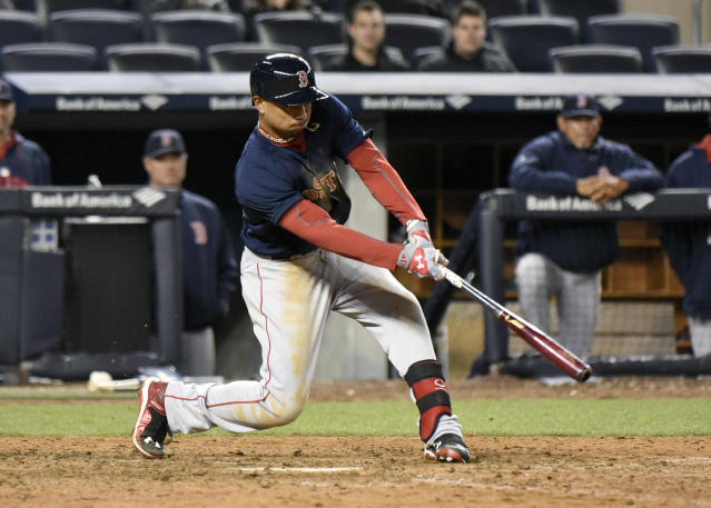 Boston Red Sox batter Mookie Betts hits a sacrifice fly to score the winning run during the 19th inning of a baseball game against the New York Yankees Friday, April 10, 2015, at Yankee Stadium in New York. The Red Sox won 6-5. (AP Photo/Bill Kostroun)