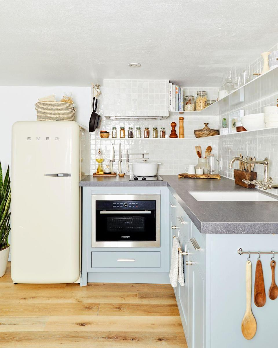 <p>Designed by Velinda Hellen of Emily Henderson Design, this kitchen uses every square each strategically. Since it's tiny, every nook and cranny matters, from the storage basket above the sink to the wall hooks on the side of the cabinet and two-tier floating shelves. </p>