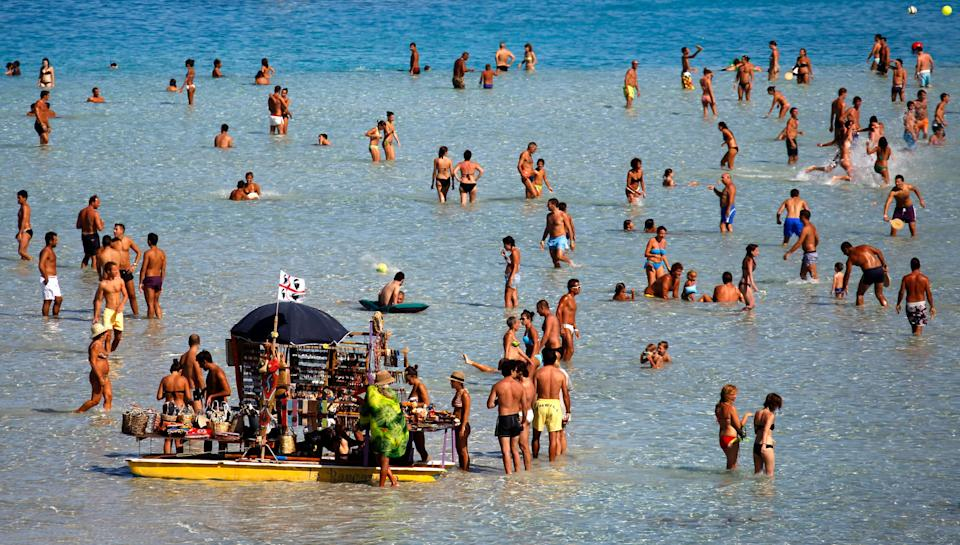 People sunbathe on the beach in the Italian town of Stintino, north west of Sardinia. (Photo: Alessandro Bianchi / Reuters)