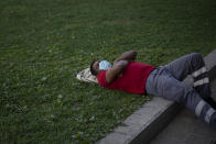 A man wearing a face mask to prevent the spread of coronavirus sleeps in a public park in Barcelona, Spain, Tuesday, Sept. 15, 2020. Spain's official death toll for the new coronavirus on Tuesday surpassed 30,000 fatalities as the country's caseload also increased beyond 600,000, becoming the first European country to overcome that threshold. (AP Photo/Emilio Morenatti)