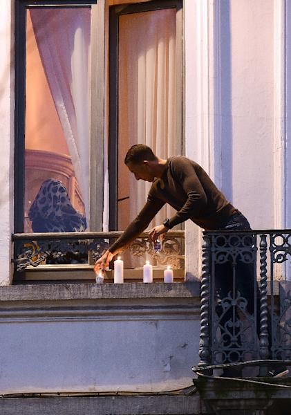 Mohamed Abdeslam, a brother of two men who helped carry out terrorist attacks in Paris, puts candles on a ledge outside a window of the family apartment in Molenbeek on November 18, 2015 (AFP Photo/Emmanuel Dunand)