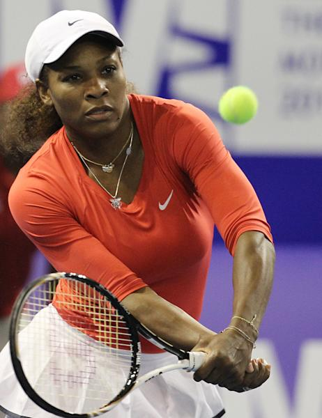 Serena Williams returns a service from sister Venus during their 'Breaking the Mould' exhibition tennis match at Ellis Park Indoor Arena in Johannesburg, South Africa on Sunday Nov. 4, 2012. Serena delivered on her promise to avenge an earlier loss to Venus, beating her 6-3, 6-4 in South Africa on Sunday for just her fourth win in 13 exhibition matches between the sisters.(AP Photo/Themba Hadebe)