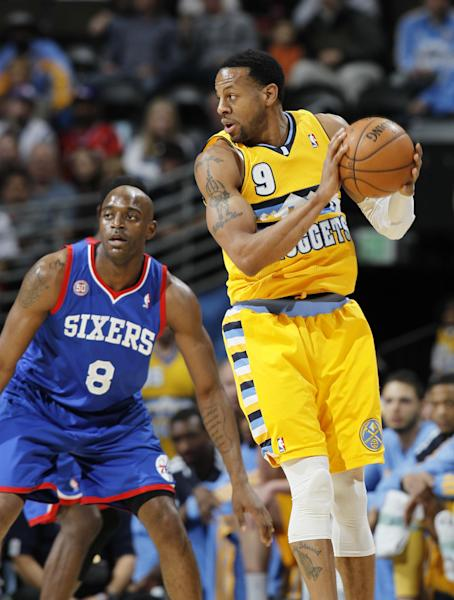 Denver Nuggets guard Andre Iguodala, right, pulls in a loose ball as Philadelphia 76ers guard Damien Wilkins covers in the first quarter of an NBA basketball game in Denver, Thursday, March 21, 2013. (AP Photo/David Zalubowski)