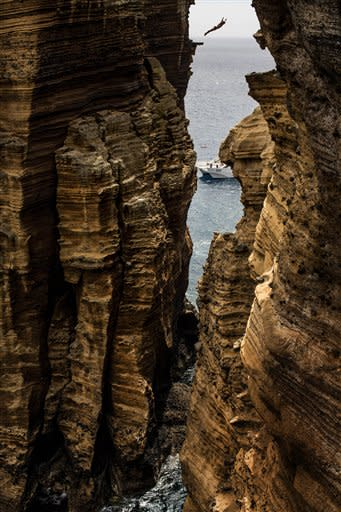 This photo made available by Red Bull shows Kent De Mond of the USA diving 29 metres from the rock monolith during the first round of the third stop of the Red Bull Cliff Diving World Series in Islet Vila Franca do Campo, Azores, Portugal, Friday July 20, 2012. Kent De Mond of the USA leads after the first round with the remaining three rounds taking place Saturday. (AP Photo/Dean Treml)