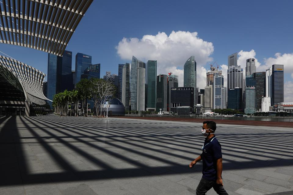 A man wearing protective mask walks at Marina Bay Sands with the Central Business District seen in the background. (Photo by Suhaimi Abdullah/Getty Images)