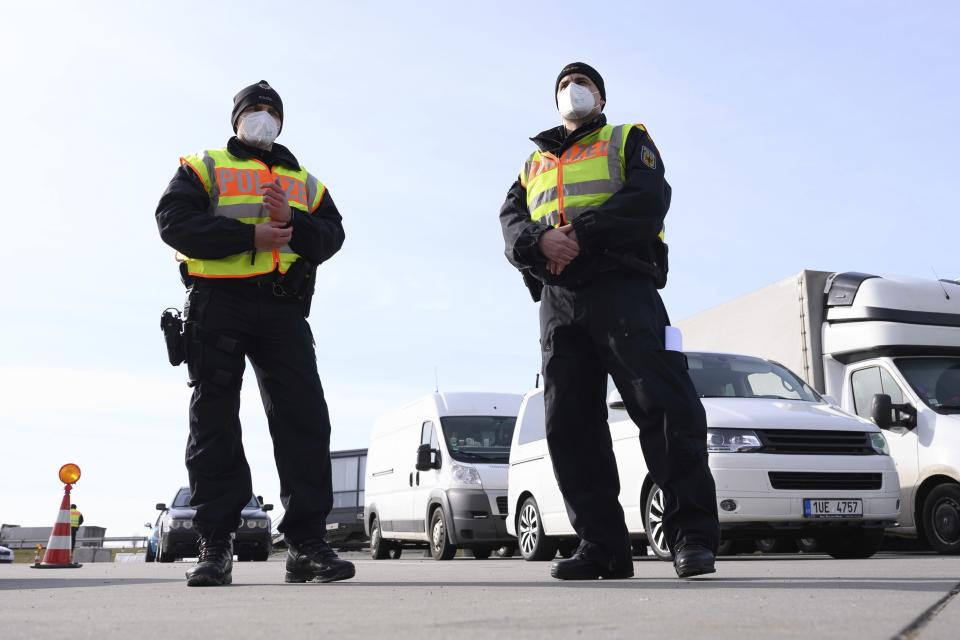 Federal police officers stand at a rest area on motorway 17 as part of border controls carried out by the Federal Police at the German-Czech border in Bad Gottleuba, Germany, Thursday, Feb. 18, 2021. On the same day, Federal Minister of the Interior Seehofer plans to inform himself about the temporary border controls. (Sebastian Kahnert/dpa via AP)