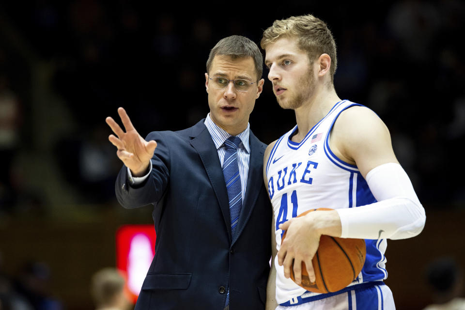 FILE - In this Dec. 19, 2019, file photo, Duke associate head coach Jon Scheyer, left, speaks with Jack White (41) during an NCAA college basketball game against Wofford in Durham, N.C. Duke Hall of Fame coach Mike Krzyzewski will coach his final season with the Blue Devils in 2021-22, a person familiar with the situation said Wednesday, June 2, 2021. The person said former Duke player and associate head coach Jon Scheyer would then take over as Krzyzewski's successor for the 2022-23 season. (AP Photo/Ben McKeown, File)