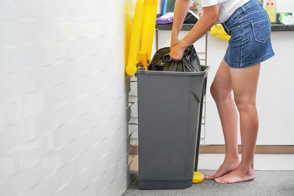 A woman takes a trash bag in the kitchen.
