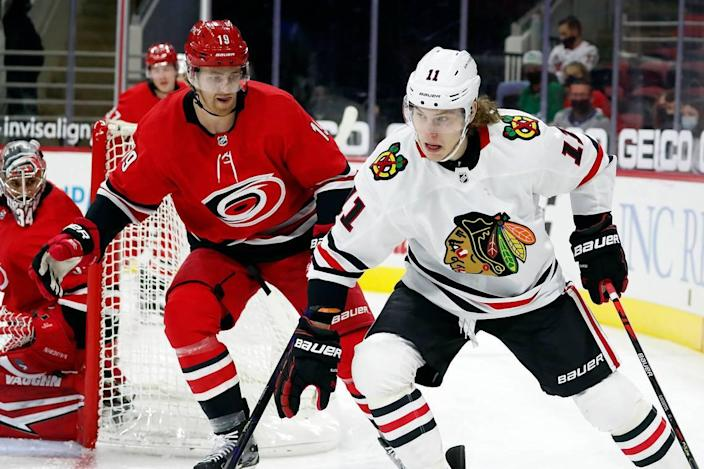 Chicago Blackhawks' Adam Gaudette (11) drives the puck around Carolina Hurricanes' Dougie Hamilton (19) during the first period of an NHL hockey game in Raleigh, N.C., Thursday, May 6, 2021. (AP Photo/Karl B DeBlaker)
