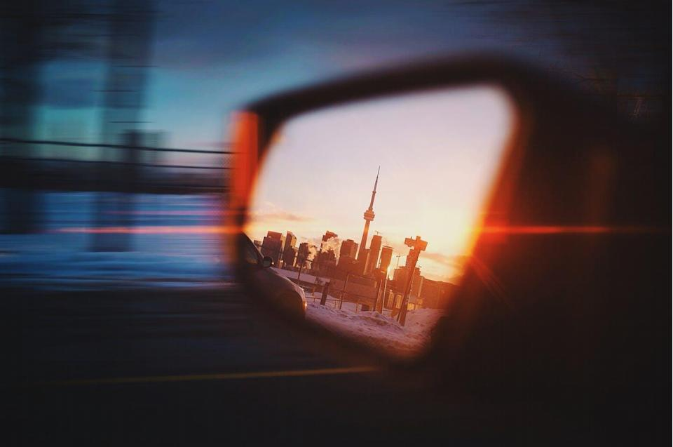 The CN Tower in the side-view mirror of a car