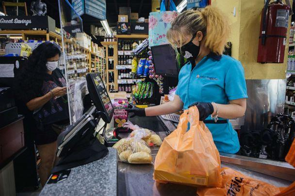 PHOTO: An employee at wears a protective face mask and gloves while ringing up a customer at a supermarket in Miami, Florida, July 8, 2020. (Jayme Gershen/Bloomberg via Getty Images)