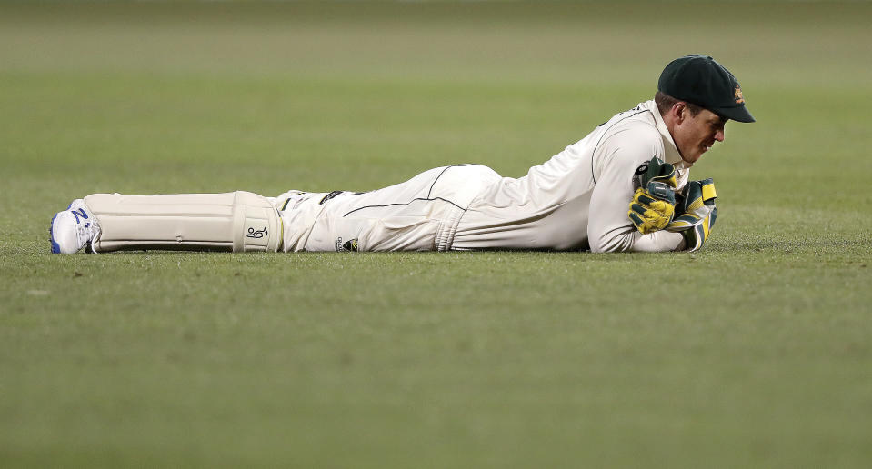 Australia's Tim Paine lays on the ground after dropping a chance to catch out India's Mayank Agarwal on the second day of their cricket test match at the Adelaide Oval in Adelaide, Australia, Friday, Dec. 18, 2020. (AP Photo/James Elsby)