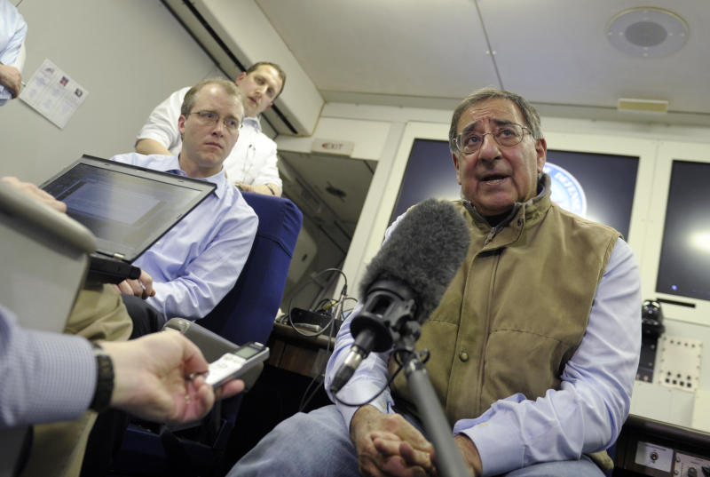 U.S. Defense Secretary Leon Panetta, right, talks to reporters while on board his plane headed to Kuwait, Monday, Dec. 10, 2012. Panetta will meet with troops as part of a visit to thank the troops for their service. (AP Photo/Susan Walsh, Pool)