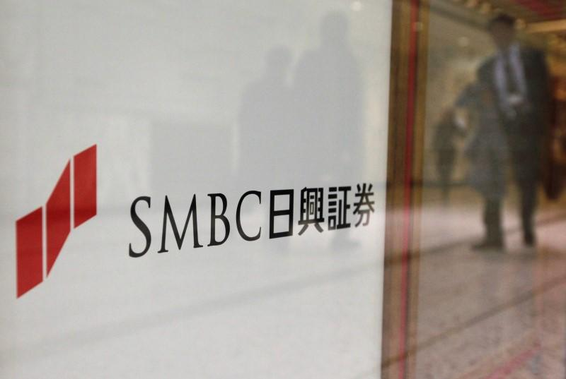 Passersby are reflected on the company logo of SMBC Nikko Securities Inc in Tokyo