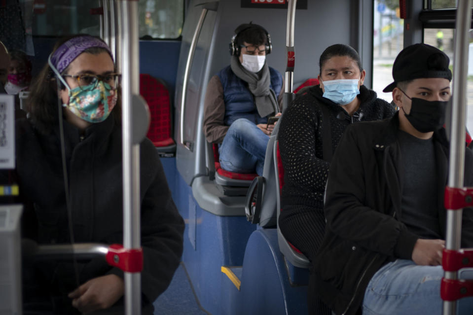 "A passenger looks at Victoria Martinez, left, as they travel in a bus in Barcelona, Spain, Monday, Feb. 8, 2021. By May this year, barring any surprises, Martinez will complete a change of both gender and identity at a civil registry in Barcelona, finally closing a patience-wearing chapter that has been stretched during the pandemic. The process, in her own words, has also been ""humiliating."" (AP Photo/Emilio Morenatti)"