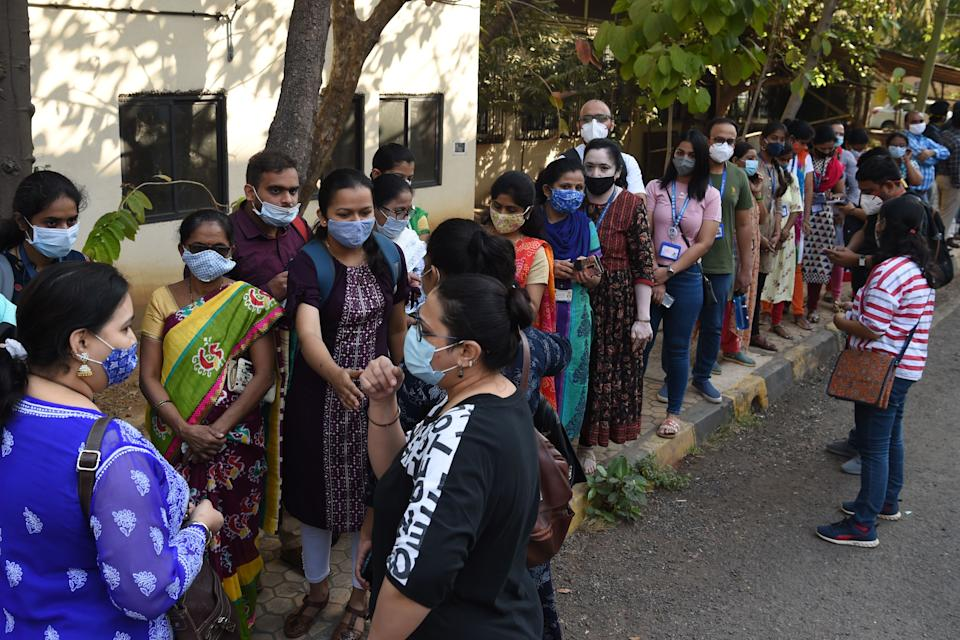 Health workers queue to receive a dose of a Covid-19 coronavirus vaccine at the Cooper hospital in Mumbai on January 16, 2021. (Photo by Punit PARANJPE / AFP) (Photo by PUNIT PARANJPE/AFP via Getty Images)