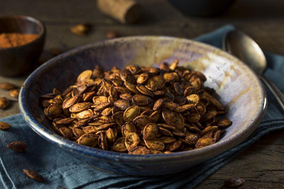 """<p>This delicious and festive snack is <strong>packed with plant-based protein</strong>. These pepitas are loaded with tons of vitamins, minerals, and antioxidants. Our Good Housekeeping Test Kitchen shares the perfect way to make them <a href=""""https://www.goodhousekeeping.com/food-recipes/cooking/a25252173/how-to-roast-pumpkin-seeds/"""" rel=""""nofollow noopener"""" target=""""_blank"""" data-ylk=""""slk:here"""" class=""""link rapid-noclick-resp"""">here</a>. </p>"""