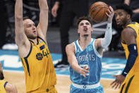 Charlotte Hornets guard LaMelo Ball (2) shoots while guarded by Utah Jazz forward Bojan Bogdanovic (44) during the first half of an NBA basketball game in Charlotte, N.C., Friday, Feb. 5, 2021. (AP Photo/Jacob Kupferman)