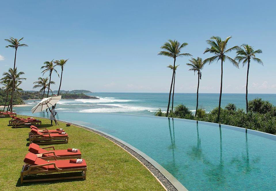 """<p>Picture yourself by this curved beauty built into a headland along Sri Lanka's spectacular south coast. Part of 39-suite <a href=""""https://www.resplendentceylon.com/capeweligama"""" rel=""""nofollow noopener"""" target=""""_blank"""" data-ylk=""""slk:Weligama"""" class=""""link rapid-noclick-resp"""">Weligama</a> resort, you might even spot a whale or two while you laze on your lounger.</p>"""